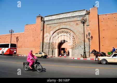 Donna velata guida di un ciclomotore passato il Bab Agnaou cancello in Marrakech, Marocco, Africa Foto Stock