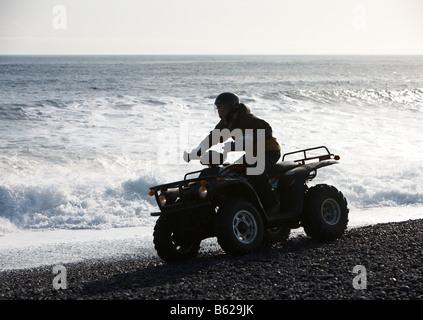 Ragazza in sella moto Quad su sabbia nera spiaggia rocciosa, Hornafjordur fiordo, Islanda Orientale Foto Stock