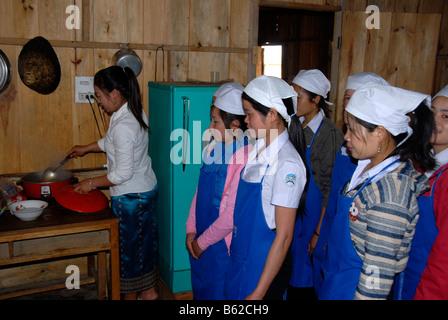 Le giovani donne di imparare a cucinare in una scuola di formazione professionale, Phonsavan, Xieng Khuang Provincia, Foto Stock