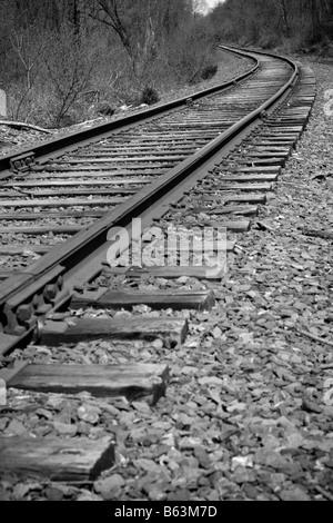 I binari della ferrovia della curvatura fuori nella distanza avanti Foto Stock