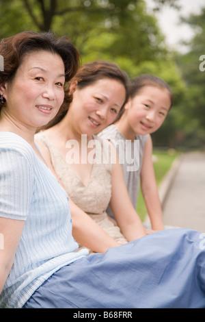 Ritratto di una famiglia composta da tre generazioni la seduta e sorridente in un giardino Foto Stock