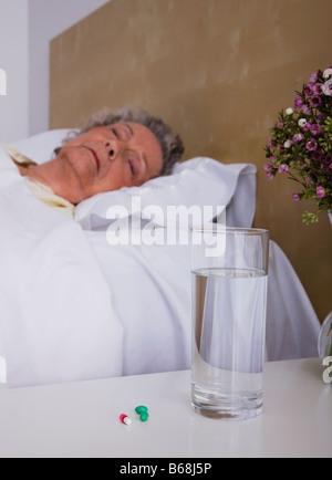 Senior donna dorme nel letto Foto Stock