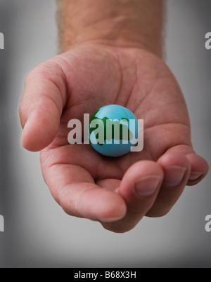 Mano d'uomo azienda piccolo globo, close-up Foto Stock