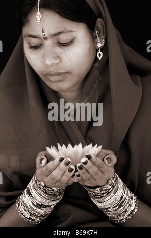 Donna indiana offre un Nymphaea ninfea tropicale Fiore. Tonalità seppia. Andhra Pradesh, India Foto Stock