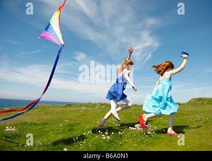 2 ragazze in esecuzione con aquiloni Foto Stock