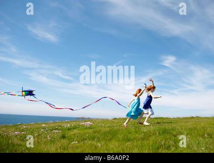 2 ragazze in esecuzione con aquiloni nel campo Foto Stock