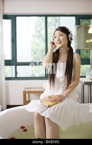 Giovane donna che indossa la cuffia e godendo di se stessa Foto Stock