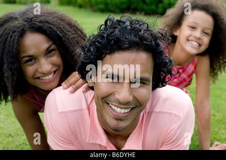 La famiglia felice. I genitori con la loro figlia sull'erba. Foto Stock