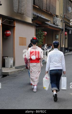 Una Maiko, un tirocinante Geisha, camminando con il suo assistente al di Odori nel quartiere di Gion di Kyoto, Giappone, Foto Stock