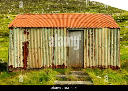 Stagno Wriggly shack, ferro corrugato edificio in Tarbeart Lewis Scozia che mostra l'età e colore Foto Stock