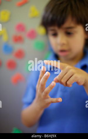 6 anno vecchio ragazzo conta sulle dita