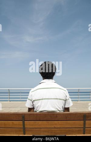 Uomo seduto su un banco in riva al mare Foto Stock