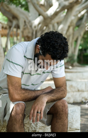 Triste uomo seduto nel parco Foto Stock