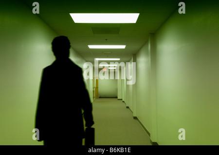 Imprenditore con valigetta camminando giù il corridoio vuoto Foto Stock