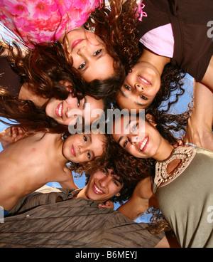 Famiglia di felici i bambini guardando in giù a sorridere all'aperto Foto Stock