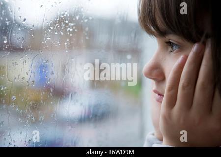 Un giovane bambino guardando fuori della finestra sul giorno di pioggia Foto Stock