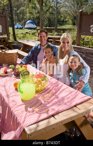 Giovane famiglia felice seduti al tavolo da picnic vicino al campeggio Foto Stock
