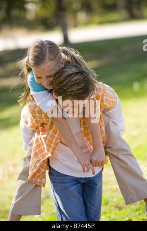 Ragazzo dando piggyback ride a ragazza in posizione di parcheggio Foto Stock