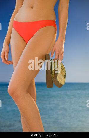 Sezione mediana della donna bikini azienda flip-flop sulla spiaggia Foto Stock