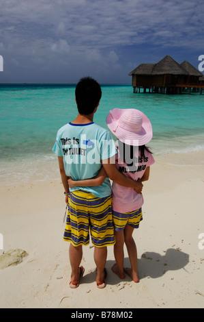 Giapponese sposini in luna di miele sulla spiaggia indossando Romeo e Giulietta T-shirt in Baros Resort, Maldive, Foto Stock
