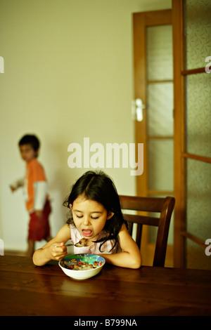 Bambina di cinque anni si siede a un tavolo di legno e si mangia una ciotola di cereale