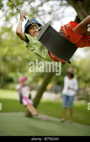 6 anno vecchio ragazzo su uno swing Foto Stock