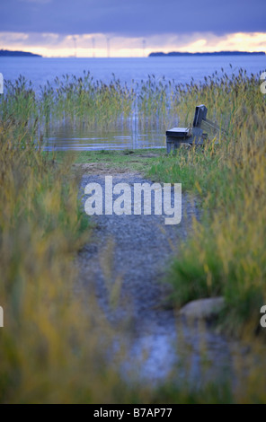 Sedile vuoto in riva al crepuscolo , Finlandia Foto Stock