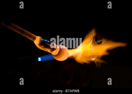 Cannello di saldatura ossiacetilenico. Scultura di vetro vicino fino a cannello ossiacetilenico. Arancione fiamma. Sfondo nero. Thailandia del sud-est asiatico Foto Stock
