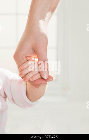 Un madri mano che tiene il suo bambino la mano. Foto Stock