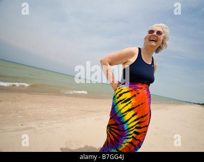 Felice sulla spiaggia: una vecchia donna vestita di un costume da bagno superiore e un colorato wrap ride e sorride Foto Stock