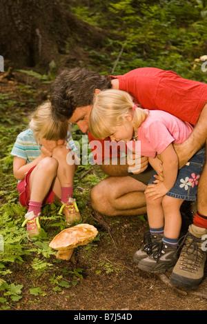 Giovane uomo esamina fungo con le figlie durante la passeggiata a lago Island Resort, Fernie, British Columbia, Foto Stock