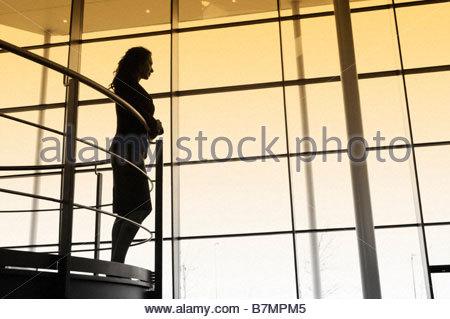 Una imprenditrice che si affaccia su un balcone ringhiere in un moderno edificio per uffici Foto Stock