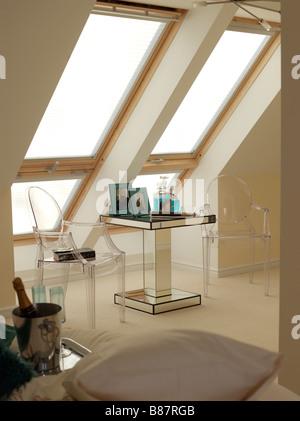 Grandi finestre Velux con un piccolo tavolo e due sedie con champagne e bicchieri Foto Stock