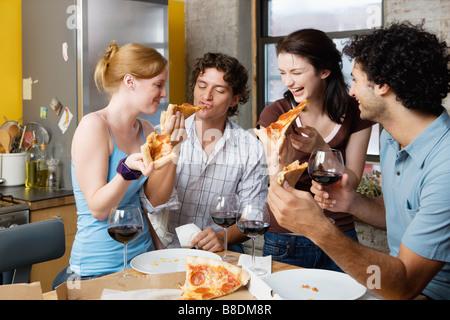 Gli amici condividono la pizza a casa Foto Stock