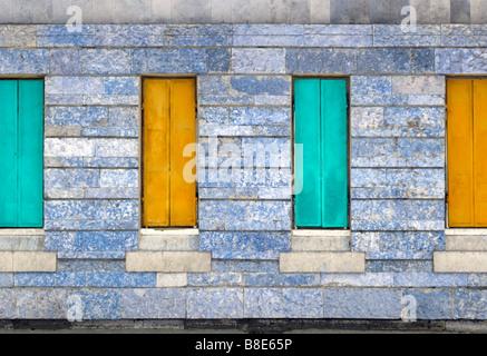 Quattro metallico chiuso le persiane della finestra sopra la pietra parete. Foto Stock