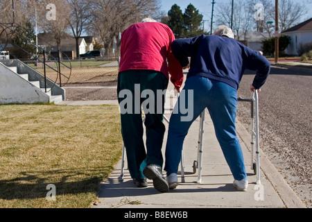 Due anziani anziani a piedi utilizzando i camminatori, la donna lo scatto l'uomo, il senso dell'umorismo umorismo, uno dei quattro in serie Foto Stock