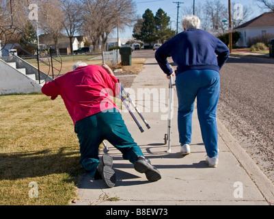 Due anziani anziani a piedi utilizzando i camminatori, la donna è scattato l'uomo che cade, divertente, 1 di 4 in serie Foto Stock