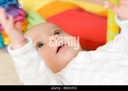 Happy baby giocando sdraiato sul pavimento Foto Stock