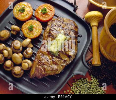 Bistecca su piastra padella con i funghi e i pomodori Foto Stock