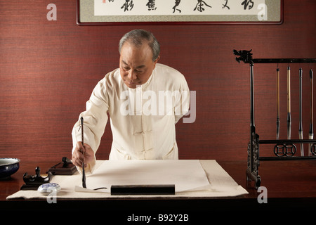 Uomo anziano praticare la calligrafia Foto Stock