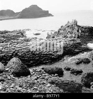 Degli anni Cinquanta, storico gruppo di persone sulle antiche formazioni rocciose, le colonne di basalto, presso il famoso Giant's Causeway, Co. Antrim, Irlanda del Nord.