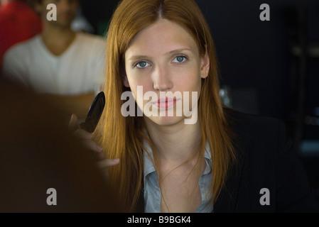 Donna che mantiene il telefono cellulare, fissando la telecamera Foto Stock