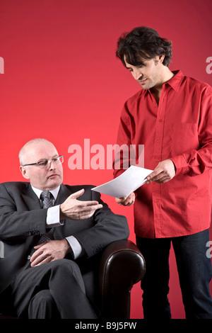 Imprenditore con un assistente, parlando di documenti Foto Stock