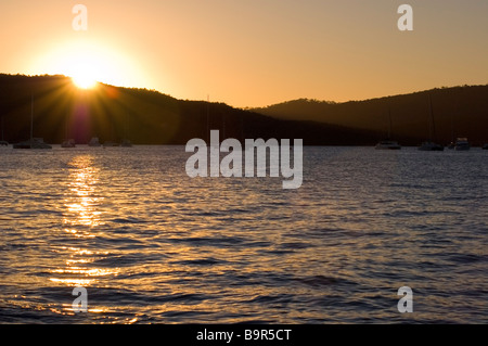 Il sole che tramonta dietro le colline sulla costa, Airlie Beach, Queensland, Australia Foto Stock