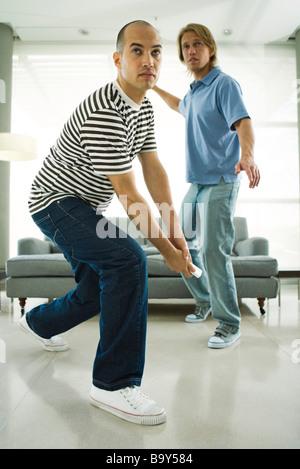 Due uomini la riproduzione del video gioco con il controller wireless Foto Stock