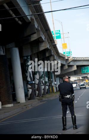 New Orleans funzionario di polizia in attesa vicino alla I-16 vicino a rampa Claiborne Avenue per indirizzare il Foto Stock