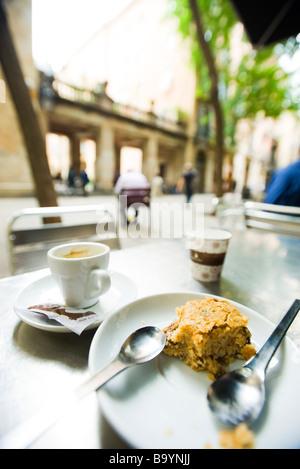 Tazza di caffè e mezza mangiato pasta sulla sinistra cafè sul marciapiede tabella Foto Stock