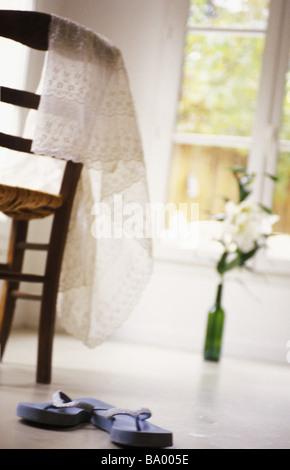 Flip-flop sul pavimento, un vaso e tavolo in background Foto Stock