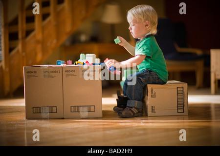 Bambino gioca con giocattoli su scatole di cartone Foto Stock