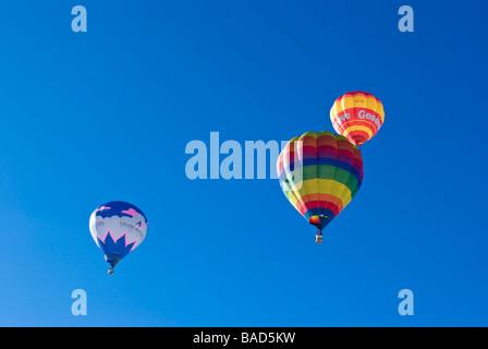 I palloni ad aria calda salga nel cielo azzurro al 2009 Chateau d'Oex International Balloon Festival / gare. Foto Stock